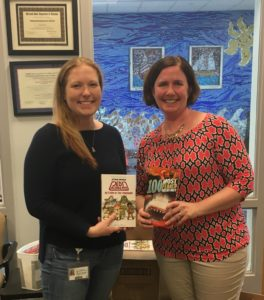 Matapeake Elementary School Reading Specialist Jenn Osborne receives new books for MES Guys Read participants from Friends of the Library President Kathie Smarick