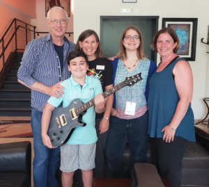 PRS Guitars founder and Managing General Partner Paul Reed Smith (left) presents a new PRS guitar to lucky Summer Reading Program winner Zander Smith (10) of Stevensville, accompanied by (left to right) Queen Anne's County Library youth service coordinator Julie Ranelli, Kent Island Youth Services Librarian Elaine Conway, and president of the Friends of Queen Anne's County Library Kathie Smarick