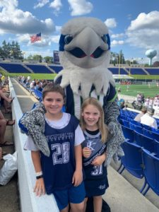 Summer Reading Program raffle winner Alexis Motto (7) and her brother Lucas (10) meet team mascot Hawkeye before the start of the Chesapeake Bayhawks game at Navy-Marine Corps Memorial Stadium in Annapolis.